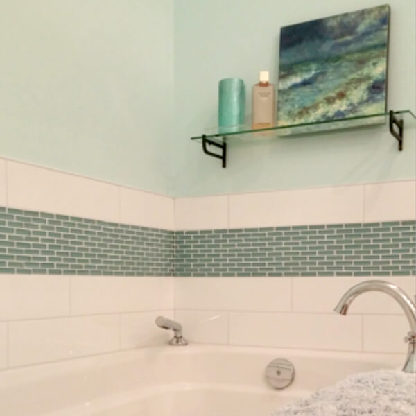 clean white tub with blue glass accent tiles