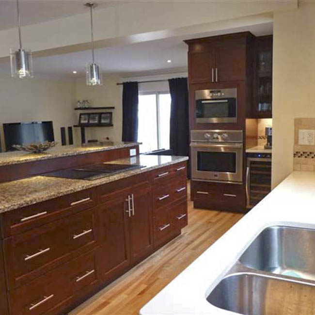Revitalized Open-Concept Kitchen stone wall dark cabinets hardwood floor