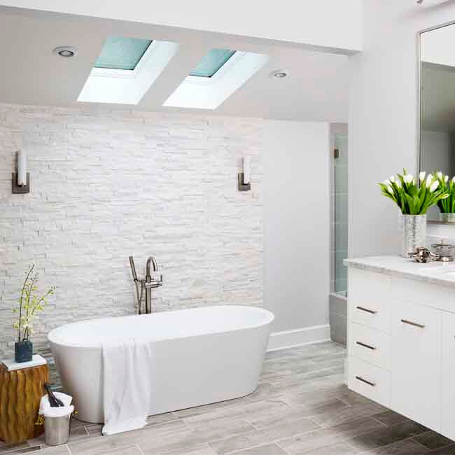 White Luxury Bathroom stand alone soake tub, floating vanity, natural stone wall, natural light from skylights - Halifax Case