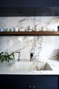 Marble countertop and backsplash with dark navy cupboards and floating wood shelf